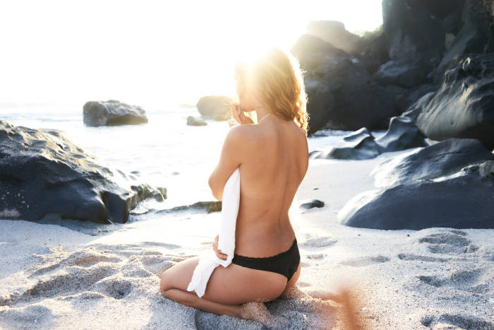 woman confidently sat on the beach after a non-surgical bum lift treatment